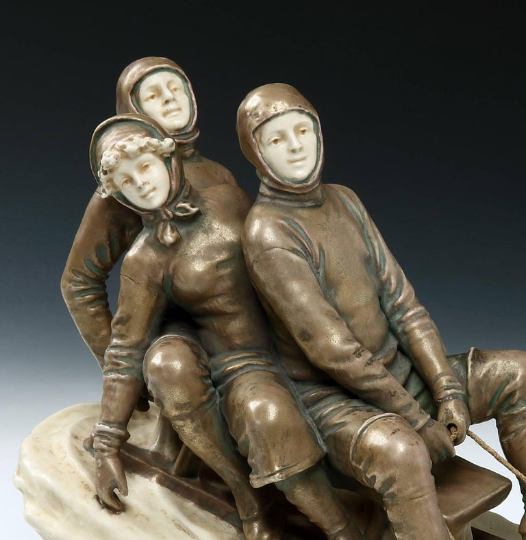 Theodore Schoop for Bernard Bloch Studios   A highly enigmatic and stylish majolica ceramic group of three figures on a wooden sled, with a male steering his female and male passenger seated behind, travelling down a snowy incline. With impressed