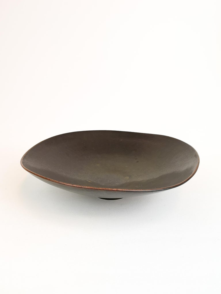 This bowl made in Sweden 1950s for Rörstrand and designed by one of the great during that period Carl-Harry Stålhane. It's a footed bowl with brown haresfur glaze. It's in good condition.   Measures D 29 cm, H 7 cm.