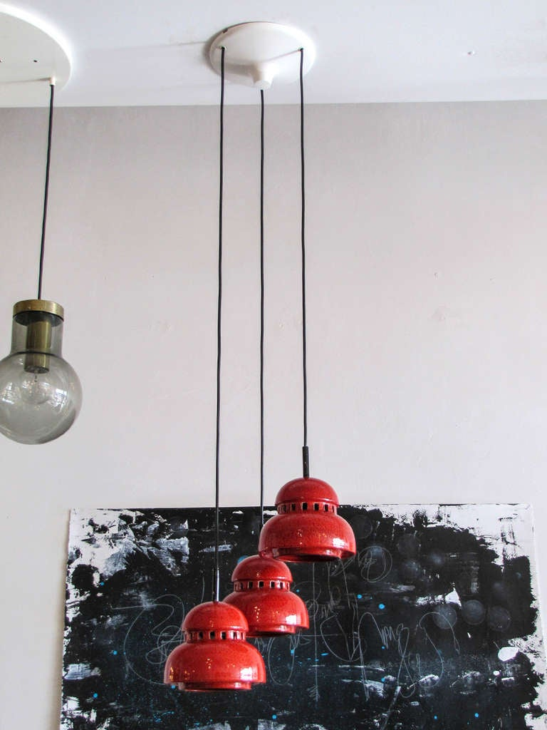 Wonderful cascading chandelier with three red ceramic pendants by Kaiser Leuchten, 100 watt per pendant capacity, cord length can be customized.