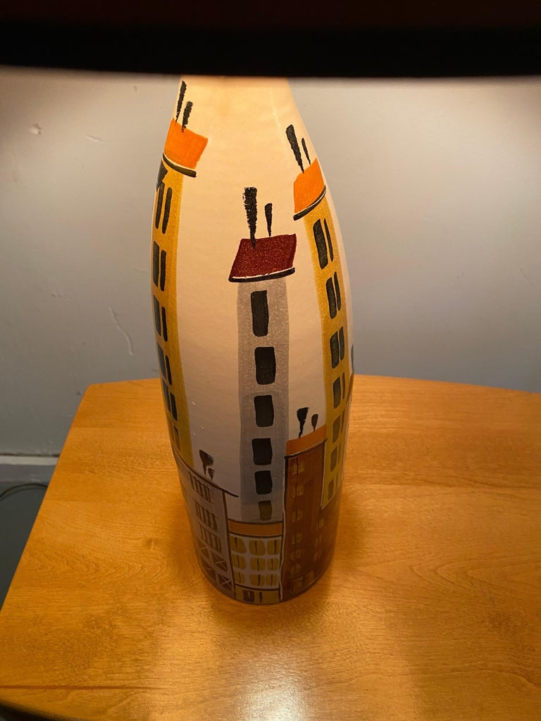 Classic Mid-Century Modern, a hand thrown tapered ceramic table lamp with an apartment building and water tower motif. Designed by Bitossi, produced in Italy, circa 1950s. Retains original shade. Height with shade 33