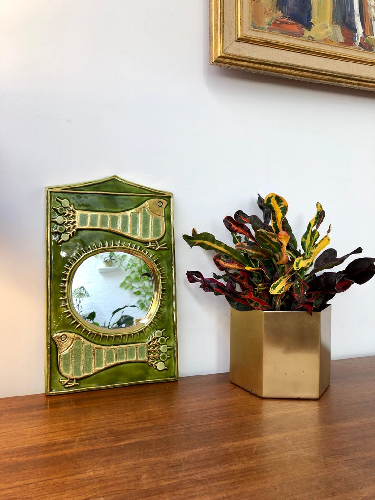 Ceramic wall mirror with green glaze (circa 1970s) by François Lembo (1930-2013). A remarkable decorative wall mirror displaying two stylised, counter-facing peacocks in gold crackle with inlaid jade-coloured enamel in geometric shapes. Separating
