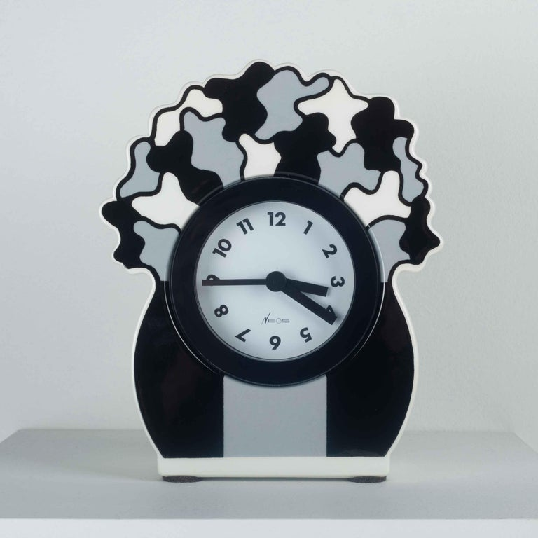 Postmodern stand clock for desk or table by George Sowden for Neos by Lorenz. Ceramic in grey black and white. Made in Italy in the 1980s.  Year: 1980s Country: Italy Dimensions: L 6.5in x H 8 in x Dm 2.75 in, L 15.5cm x H 20.3cm x D