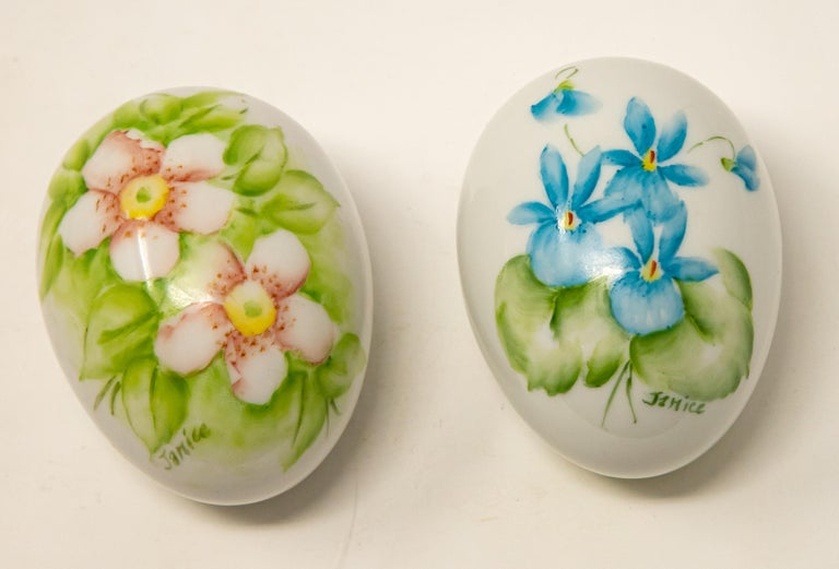 Offering a pair of ceramic hand painted eggs. Both are cream in color. One has light pink florals with greenery around them, and the other is blue florals with greenery. Both are signed Janice, and the bottoms are marked, hand painted by Janice