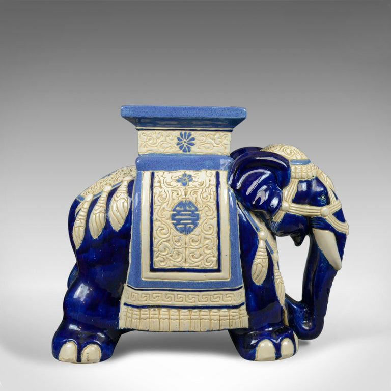 This is a ceramic elephant plant stand or garden companion table dating to the mid-late 20th century.  A large piece offering a stabile platform at 44 cm (17.25