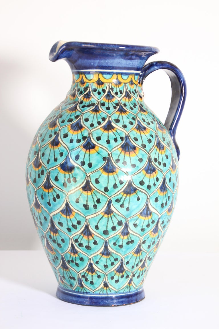 Glazed polychrome ceramic pitcher peacock blue design.