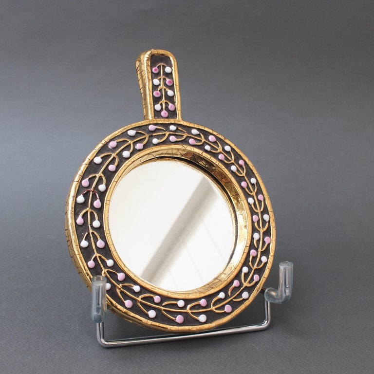 Ceramic hand mirror with flower bud motif by François Lembo, circa 1960s. An elegant piece of decorative art consisting of a lustrous gold craquelure outer and inner frame. Between the craquelure is chocolate-brown ceramic with a gold flower bud