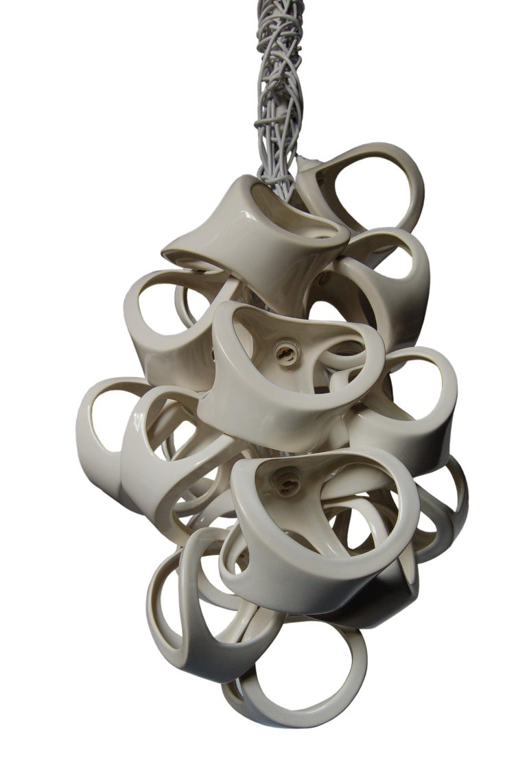 An organic grouping of 18 slip cast ceramic shades. The bone like forms nest together to form a sculptural fixture with dramatic shadows. White knotted cords accentuate the organic nature of the Ceramic Lamp series. Overall length of piece can be