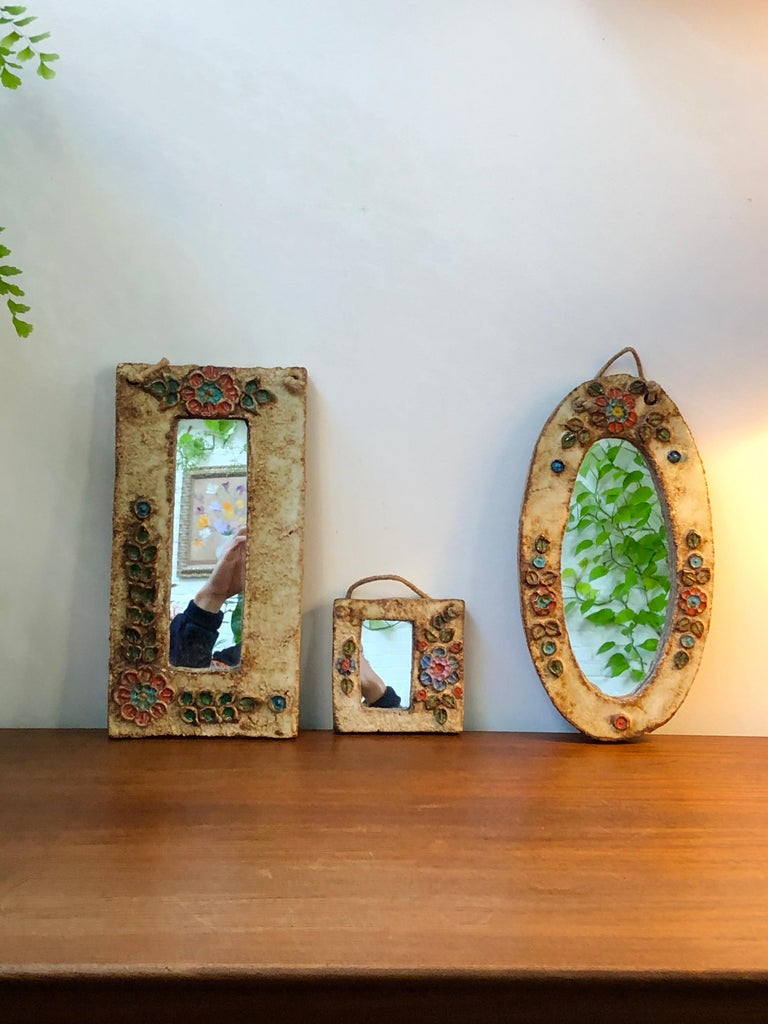 Ceramic flower-motif wall mirror with glazed leaves attributed to La Roue, Vallauris, France (circa 1960s). A charming, decorative small mirror with rustic but colourful details surrounding the oval mirror. In good vintage condition showing
