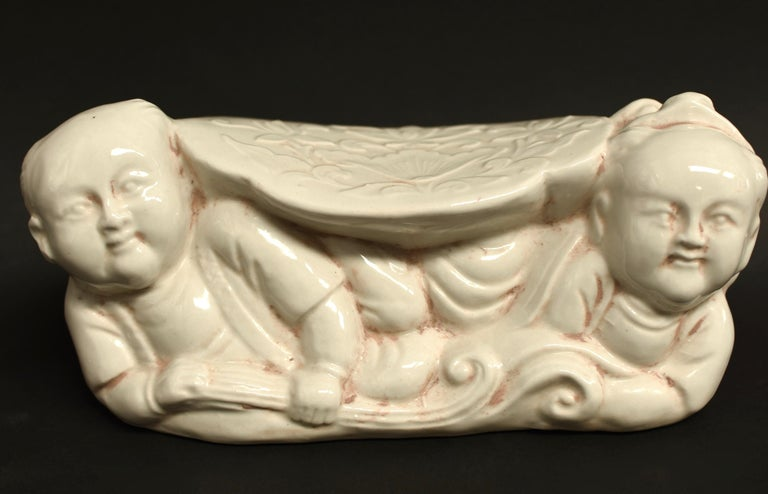 A song dynasty style ceramic pillow of the Ding kiln. The Ding kiln is one of the most important Song dynasty kilns. It produces milky white or beige glazed pieces that are favored for their simplicity and country grace. A pair of cherub boys raise