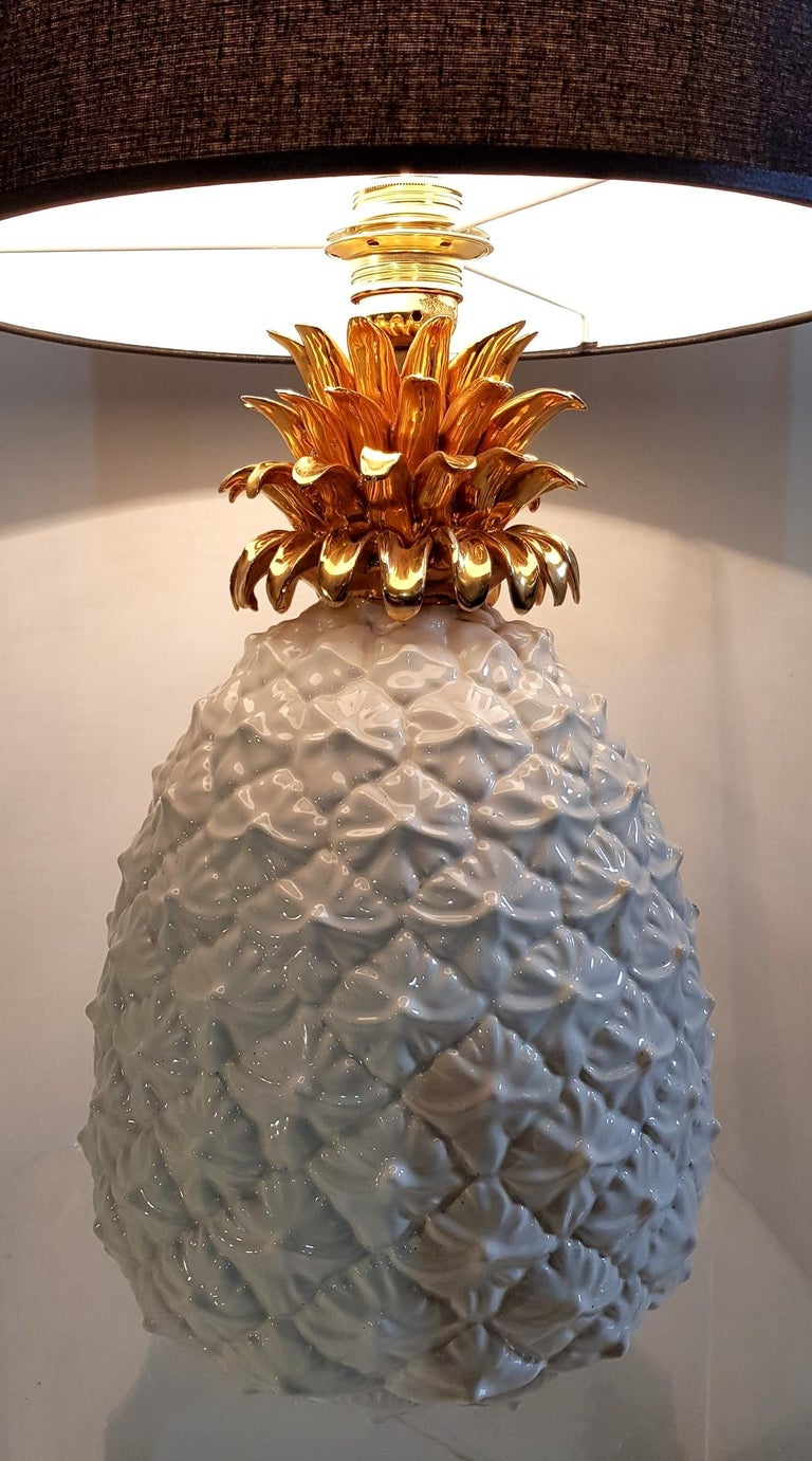 A glam 1970s vintage table lamp made in Italy. It has a pineapple shaped base made from white and gold glazed ceramic topped with a black cotton lampshade.