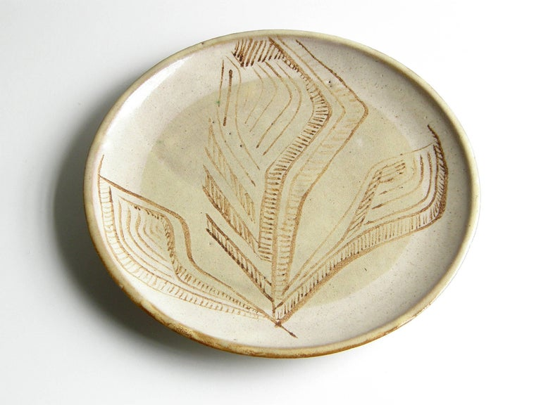 This ceramic platter by Lee Rosen for Design Technics is a functional decorative art object. It's lovely to look at, and it also makes an excellent serving plate or tray. The hand painted, abstract floral design in the glaze is a nice blend of