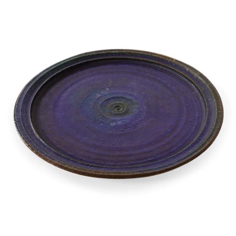 A hand-thrown studio-made by Raija Tuumi for Arabia, Finland. Stoneware platter with a rustic and textured purple and blue glaze.