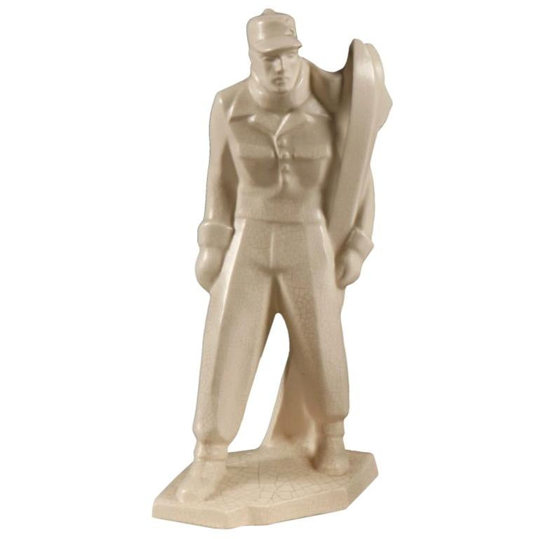 A fine ceramic Art Deco sculpture of skier holding his skis, in period dress, the whole on a square base in white craquelure glaze.   With a moulded mark of LE JAN to the rear of the base. .
