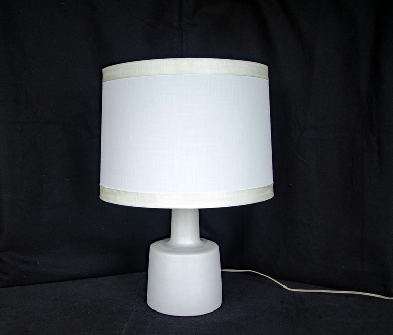Very nice smaller size table lamp with an antique white ceramic base and signature walnut finial. The Martz signature is on the back of the ceramic base near the cord. A perfect lamp for a desk, dresser, or bedside table. The white base has a matte