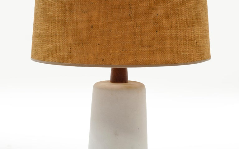Table lamp designed by Gordon Martz. Ceramic body in off white and tan / taupe with the original shade and walnut finial. Signed Martz. Measures: Shade diameter 16 inches, base diameter 7 inches.