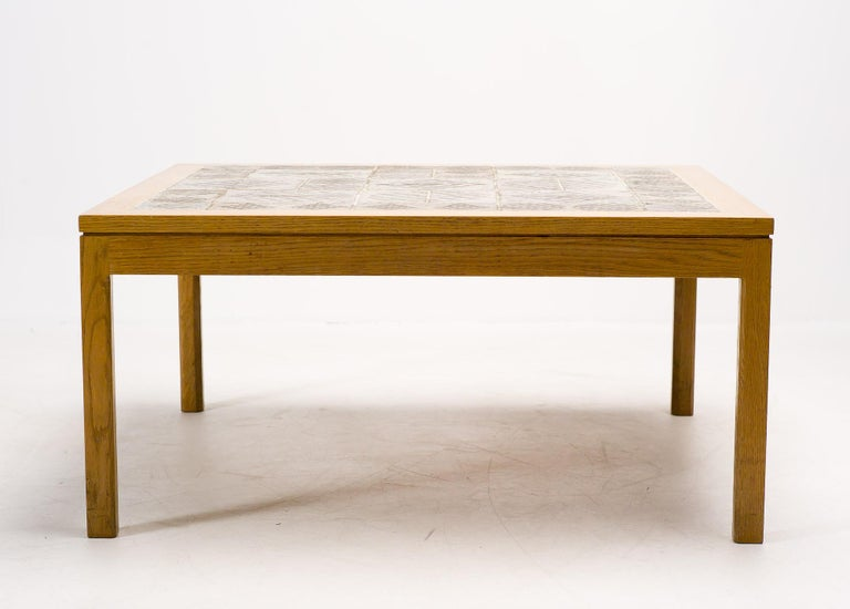 Square coffee table by Wørts & Poulsen with ceramic tile top laid inside an ash table frame.  The tiles are handcrafted by the Danish ceramicist Tue Poulsen. One tile is signed