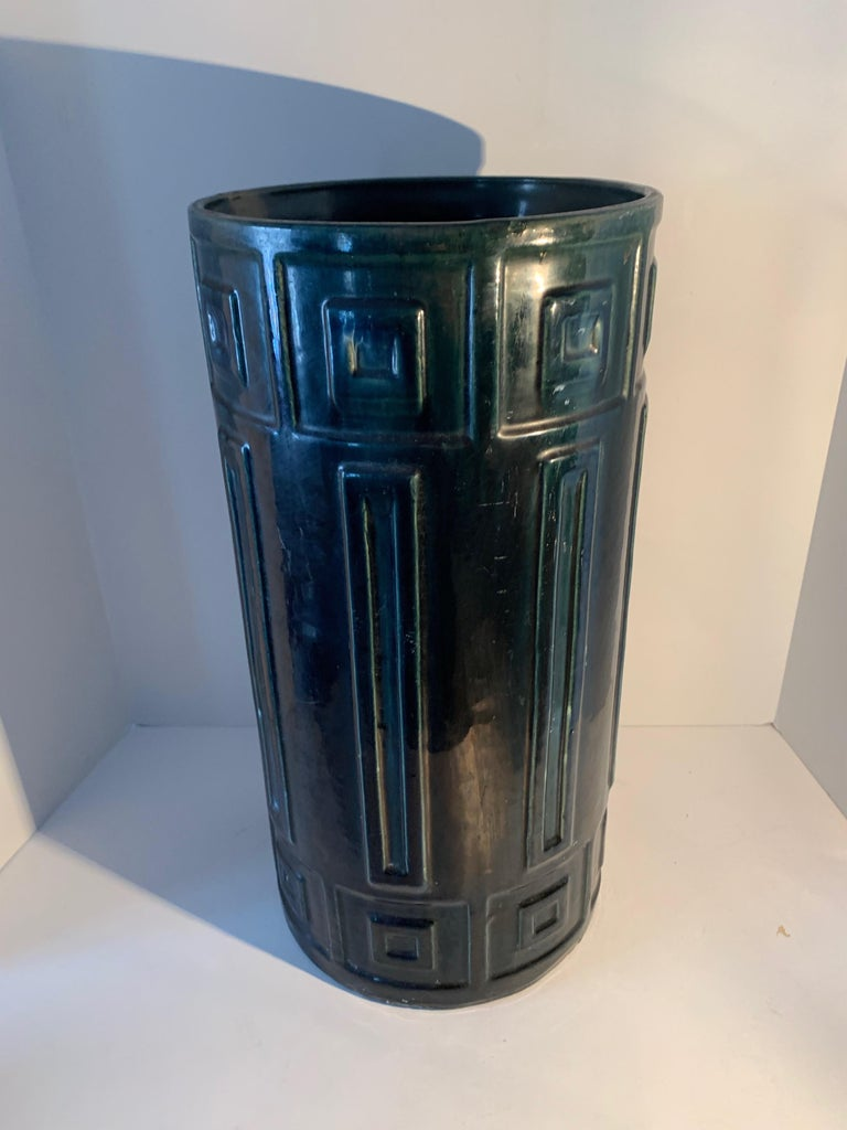 Ceramic umbrella stand in a heavy and unique hue in the blue / green family. The piece has unique markings, reminiscent of a Greek key, however they are a succession of squares. A wonderful piece at any entry for umbrellas or walking sticks. Weight