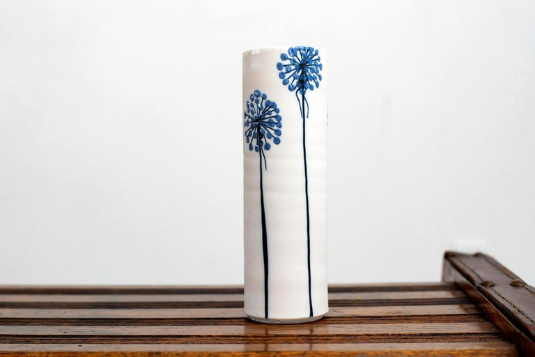 Gorgeous ceramic vase by Alan et Lyn Newton- Cylindrical earthenware ceramic with simple blue flower hand painted.