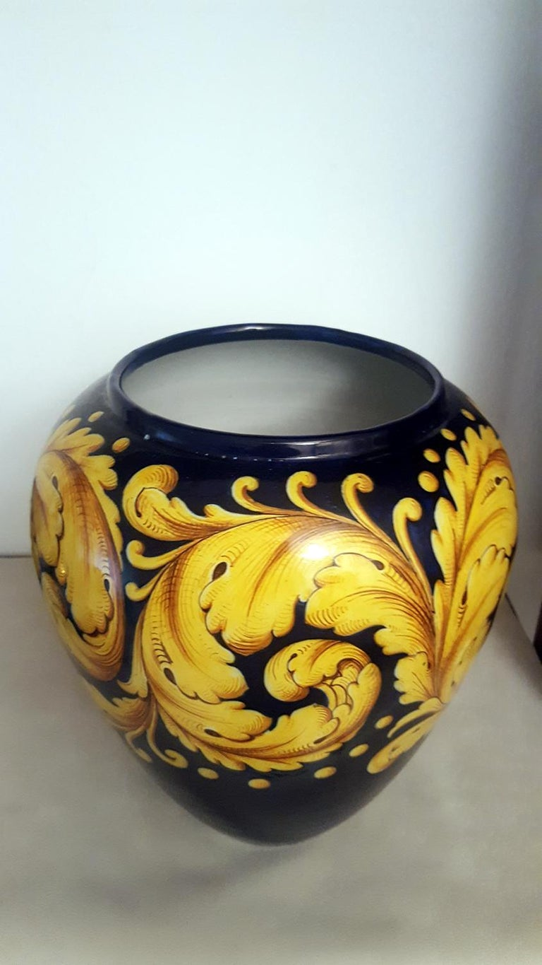 Beautiful ceramic vase manufactured by Ginori, signed. On a beautiful and rare cobalt-blue background Baroque volutes of leaves are designed in golden yellow very well shaded. The ceramic is in perfect original condition, without any damage or