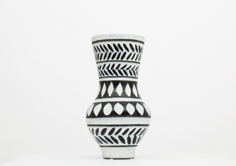 This ceramic vase is created by Roger Capron. Capron was a ceramicist mainly based in Vallauris, a village of potters in the south of France during the 1950s. This patterns/drawings on this vase is very representative of Capron's body of works