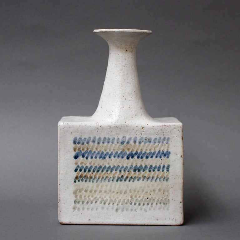 Ceramic vase with geometric line design by ceramicist Bruno Gambone, (circa 1970s). This elegantly shaped narrow-opening flower vase is a work of art. With a modern rectangular base and lean neck its shape has its origins in primitive works. A