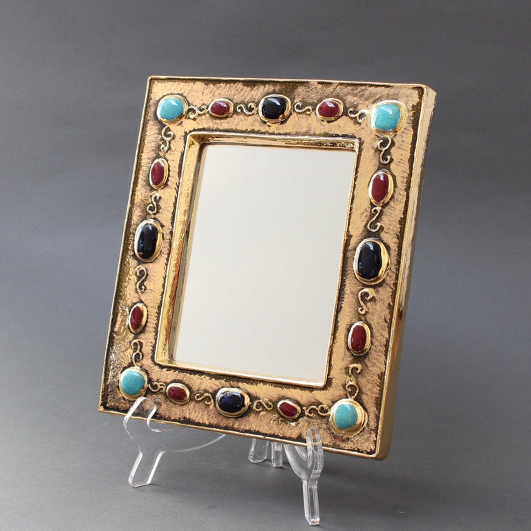Inspired by Byzantine iconography, a rectangular, gilded glazed ceramic wall mirror by François Lembo (circa 1960s-1970s). With enamelled ceramic cabochons in alternating colours of black, ruby red and turquoise, it is an unusually elegant piece of
