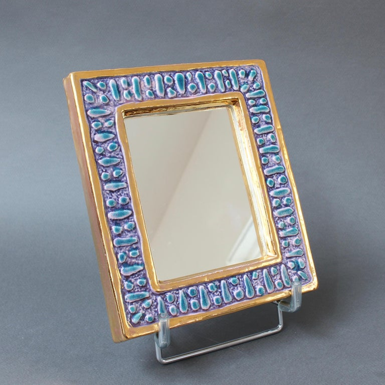 A diminutive ceramic wall mirror with blue enamel glaze and abstract motif (circa 1970s) attributed to François Lembo. A whimsically decorated wall mirror with gold colored inner and outer borders framing a lustrous blue and magenta enamel in a