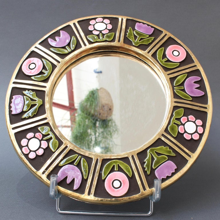 Ceramic wall mirror with flower motif (circa 1960s), by François Lembo (1930-2013). A porthole-shaped decorative wall mirror delights the eye. The inner and outer frames are in a stunning gold craquelure. The enameled flowers are superimposed over a