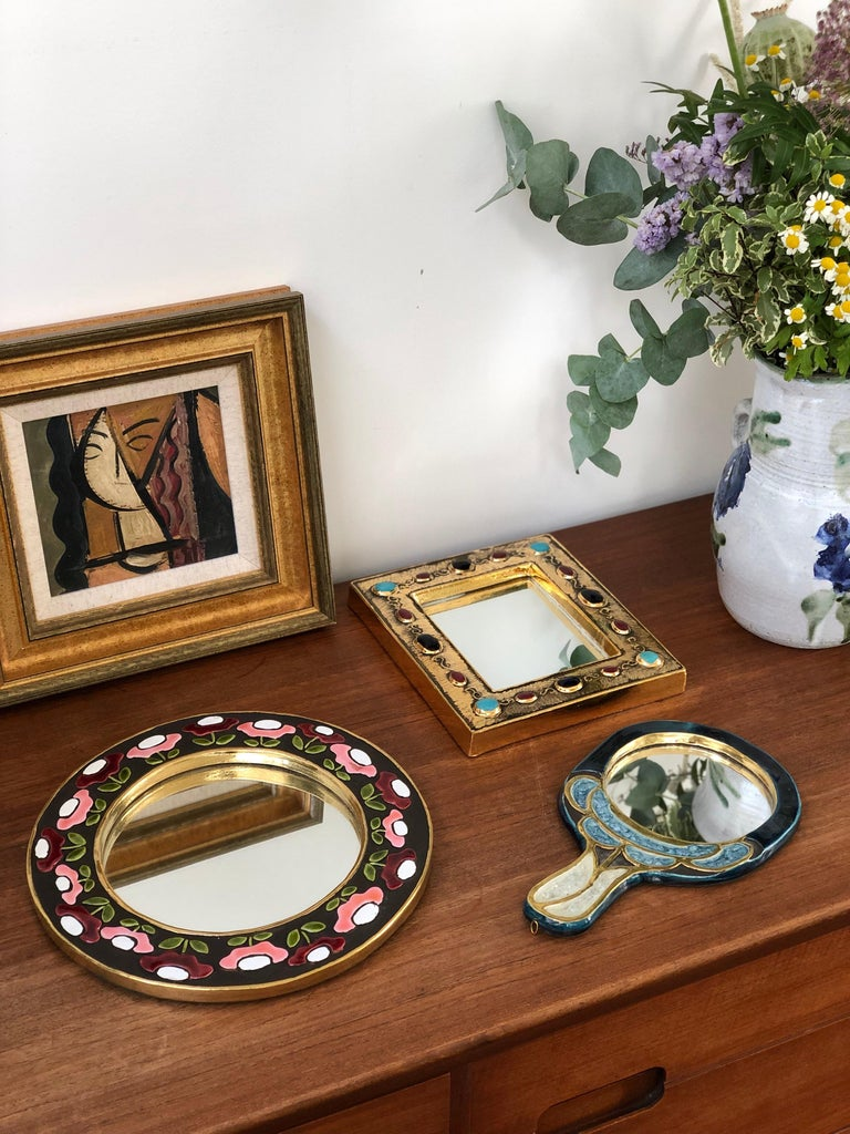 Ceramic wall mirror with flower motif (circa 1960s), by Mithé Espelt. A porthole-shaped decorative wall mirror delights the eye. The inner and outer frames are in a stunning gold craquelure. The enamelled flowers are superimposed over a chocolate