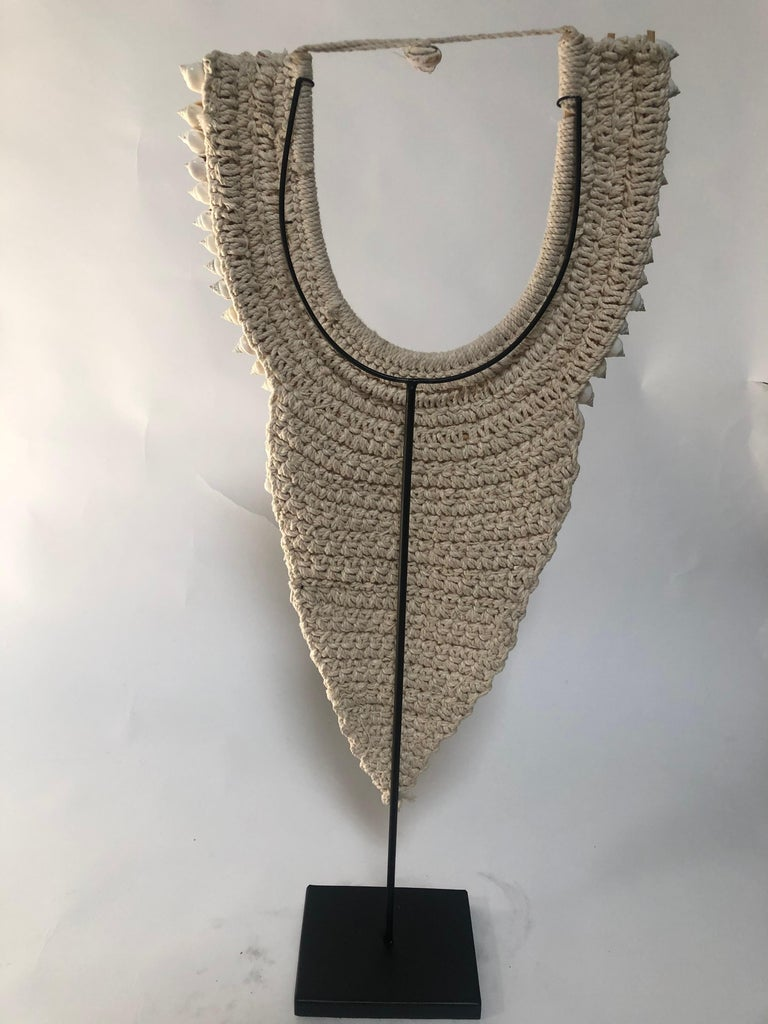 Detailed shell necklace on stand.