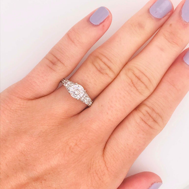 This vintage styled diamond engagement ring has a 1.01 carat round brilliant, Hearts & Arrows diamond set in the center! The 14 karat white gold, vintage/antique designed ring has the most beautiful and intricate design with diamonds going half way