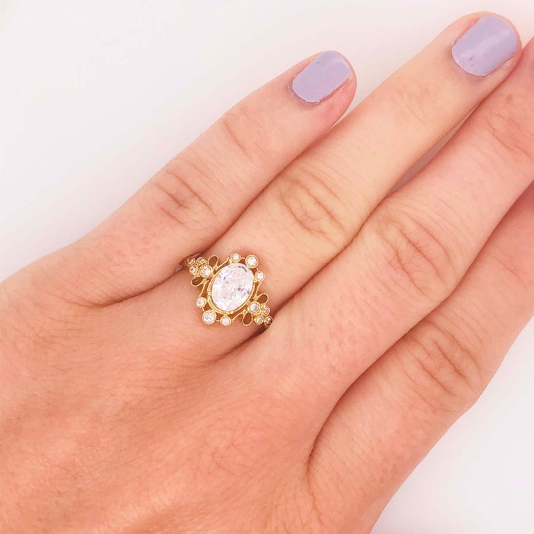 This gorgeous antique style engagement ring has an oval diamond set in the center of a gorgeous handcrafted frame. The oval diamond is a certified diamond with its original report. The oval diamond is 1.20 carat! With a G color and SI-2 clarity.