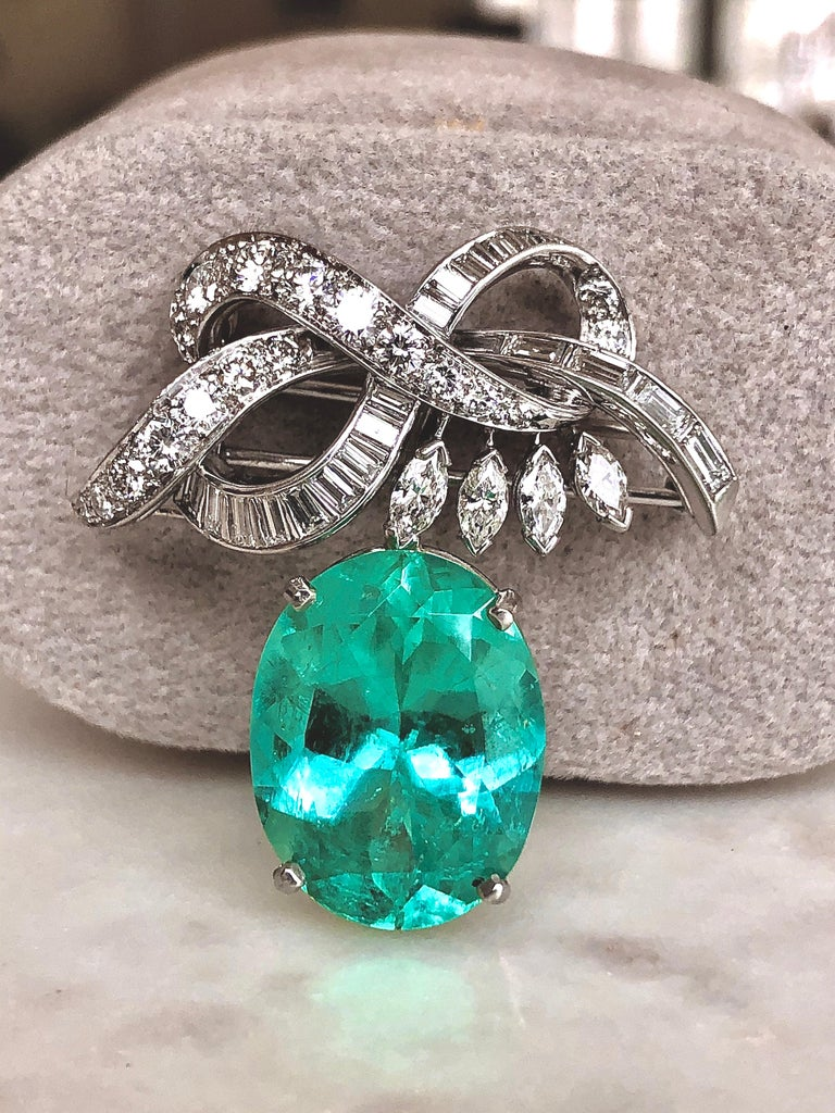 An exquisite brooch features an oval cut Colombian emerald weighing 16.16 carats set in a ribbon motif brooch. The ribbon is set with tapered baguette, step-cut diamonds, marquise cut diamonds and graduated brilliant-cut diamonds (Excellent VS1