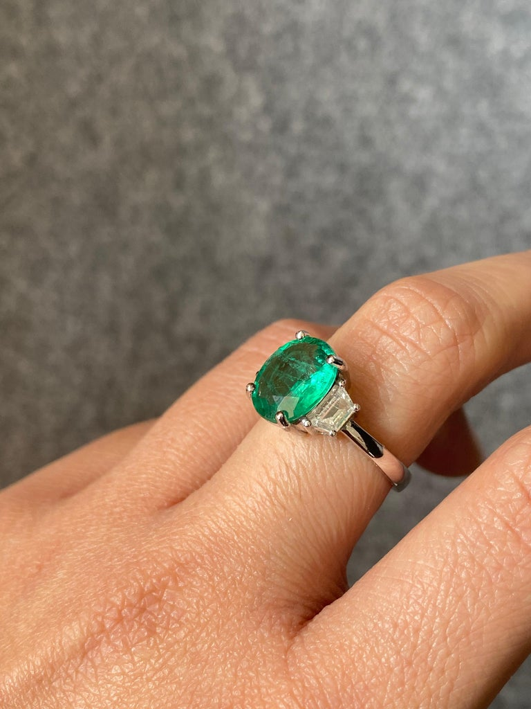 A beautiful oval-shape Zambian Emerald stone, weighing 2.56 carats - transparent with very few inclusions. It's a vivid green Emerald, which is an ideal color for the stone. The 2 trapezoid Diamonds are colorless, VS quality and weigh 0.44 carats in