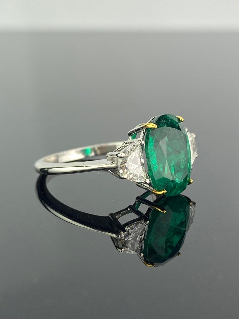 A beautiful three stone engagement ring, with a 2.68 carat transparent natural Zambian Emerald centre stone and 0.53 carat half-moon side stone diamonds. The emerald is of great lustre and has an ideal colour with very few minor inclusions. All set