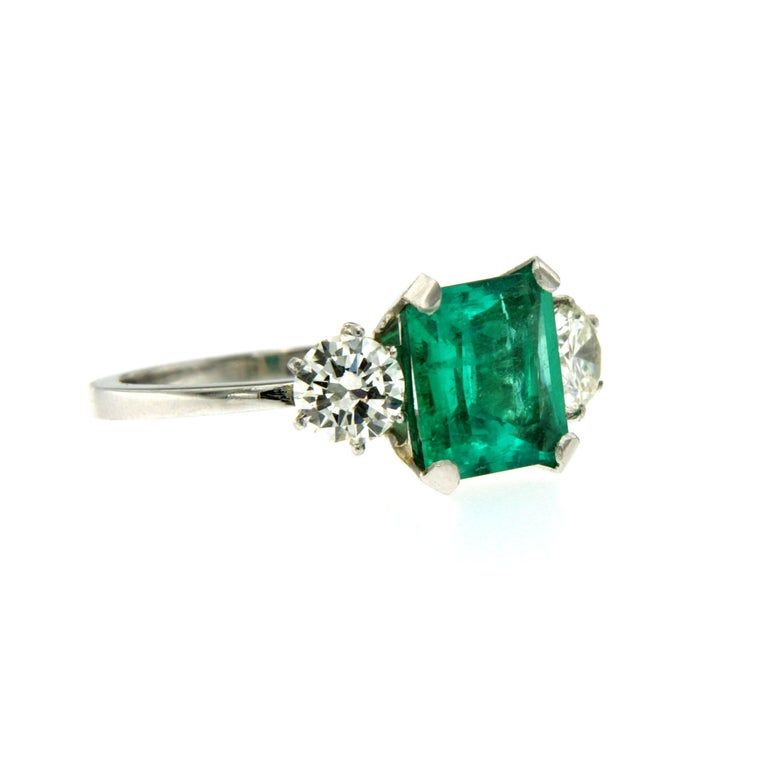 A beautiful and classy Platinum engagement ring showcasing a natural certified Colombian Emerald approx. 2.75 carats of great quality, surrounded by approx. 1.10 carat of Old mine cut diamonds graded I color Vvs. Origin Italy, circa 1980  CONDITION: