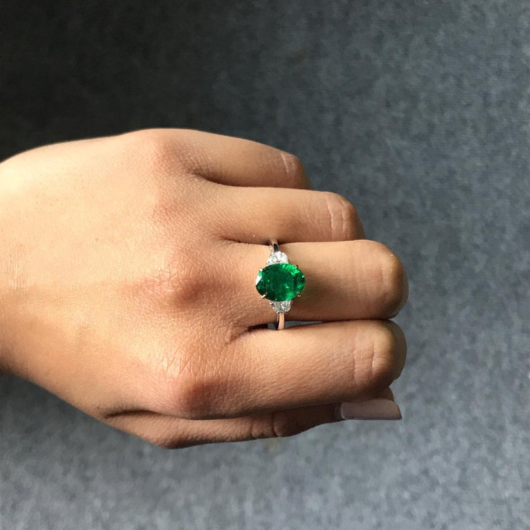 A classic three stone ring, with a 3.22 carat high quality and great colour oval cut Zambian Emerald centre stone and 2 half-moon 0.36 carat side stone Diamonds. Currently a ring size US 6, but we can resize the ring for you without additional cost.