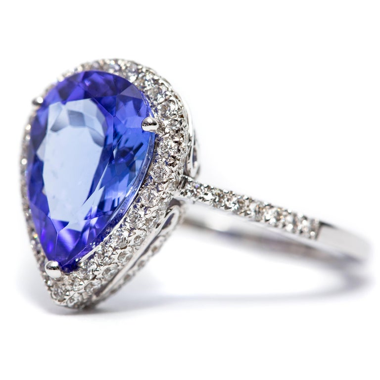 A beautiful 3.26 Carat Pear shaped Tanzanite halo engagement ring featuring 0.75 Carats of white Color G Clarity VS1 Round Brilliant Cut Diamonds. Set in 18 Karat White Gold.  UK size - N, US size - 7 available in other carat sizes as well as ring
