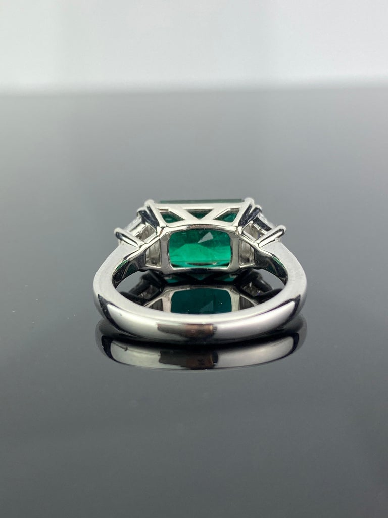 A stunning 3.42 carat emerald cut Zambian Emerald and 0.44 carat VS quality, G color White Diamond three-stone engagement ring. The Emerald is transparent, with very few naturally occurring inclusions. The cut of the stone is excellent, there is