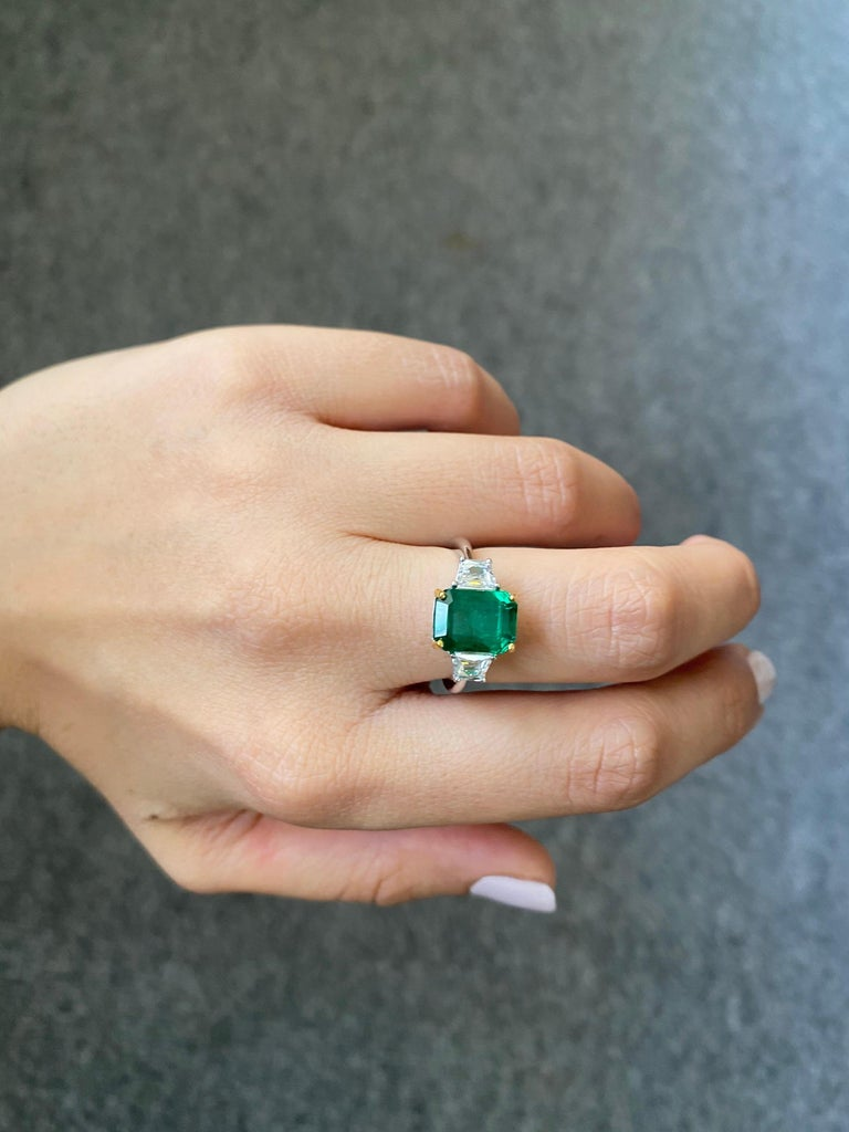 An absolutely stunning Zambian Emerald stone, weighing 3.82 carats - transparent with very few inclusions, and great luster. It's a vivid green Emerald, which is an ideal color for the stone. The 2 trapezoid Diamonds are colorless, VS quality and
