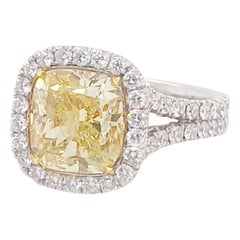 Certified 4 Carat Fancy Yellow Diamond and White Diamond Halo 18 Karat Ring