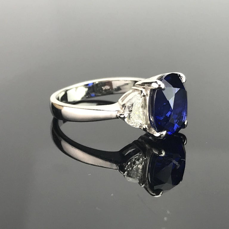 A classic 3-stone ring using Sri-Lankan, eye clean, vivid blue Sapphire as the centre stone, with 2 half-moon diamond side stones (0.87 carats total).  Stone Details:  Stone: Sri Lankan Sapphire Carat Weight: 5.06 Carats  Diamond Details:  Total