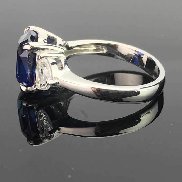 Oval Cut Certified 5.06 Carat Vivid Blue Sapphire and Diamond Three-Stone Ring For Sale