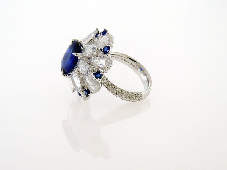 A stunning cocktail ring featuring 5.11 carat oval blue sapphire and diamonds mounted in 18K white gold. The sapphire is certified by SSEF (Swiss Gemological Institute), certificate # 97335 stating no indication of heat. 16 round diamonds weighing