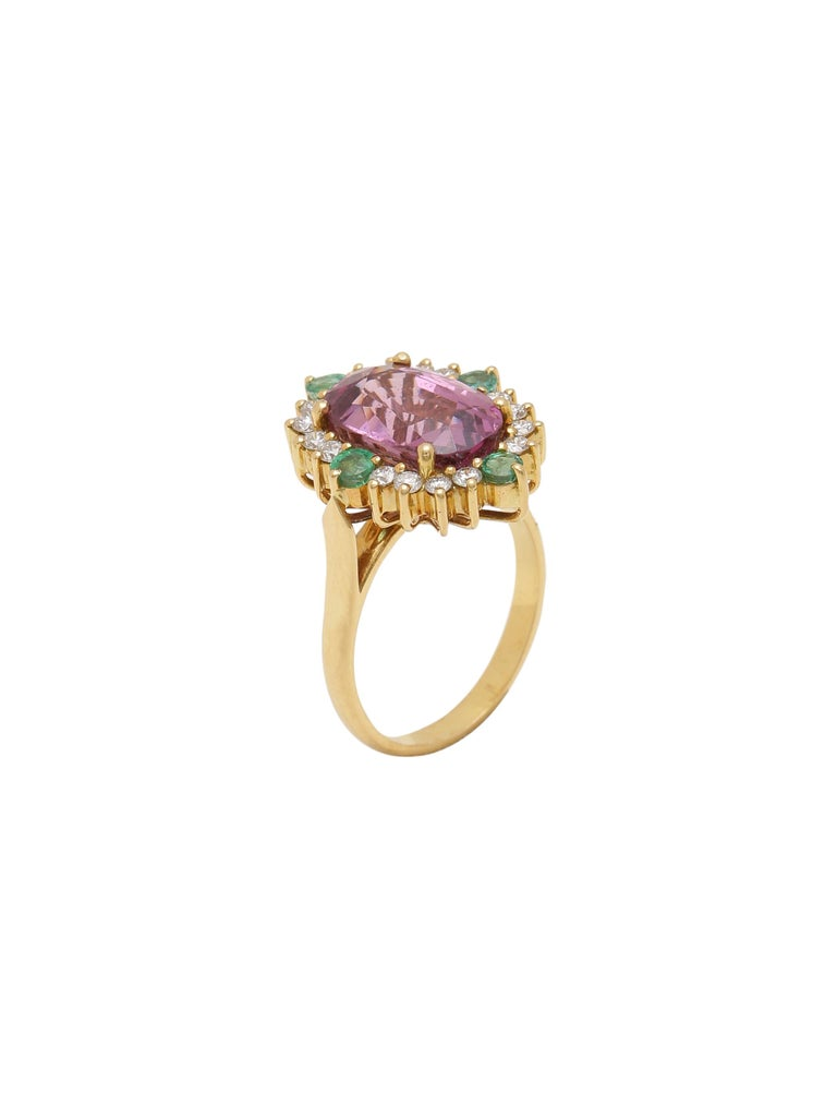 A beautiful ring with a stunning 5.80 carats Natural Spinel with a halo of high quality white diamonds around. You will also notice 4 natural round emeralds with nice lustre complimenting the centre Spinel.  The Spinel is certified from a renowned