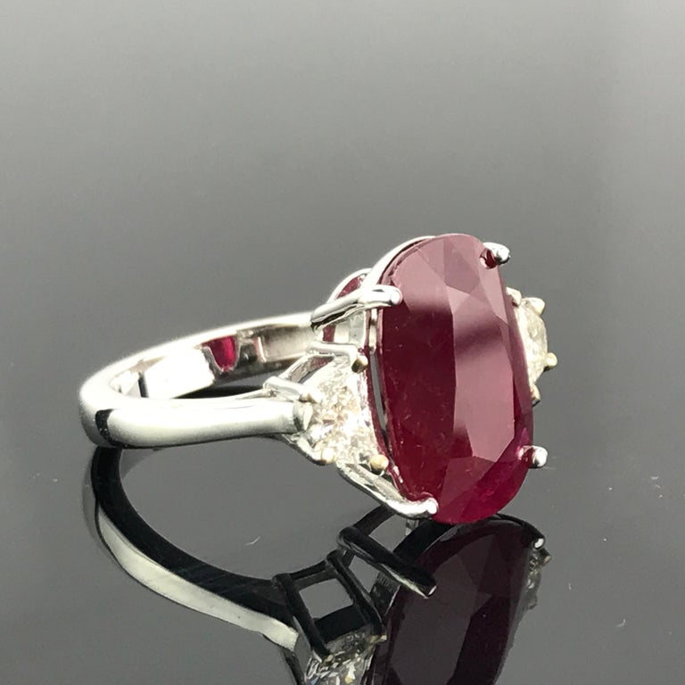 A gorgeous 7.85 carat, oval shaped, Burmese Ruby ring with 2 half-moon 0.74 carat White Diamonds, all set in 18K White Gold. Currently a ring size US 6, but we can resize the ring without additional cost. Link to a video of the ring can be