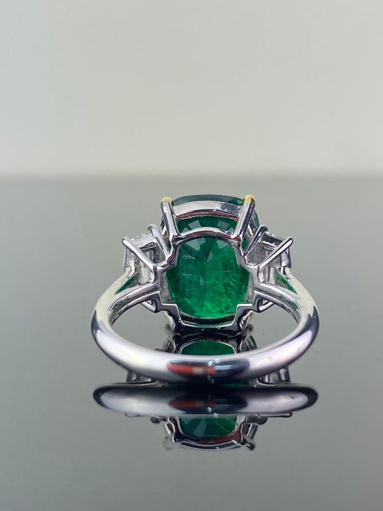 A classic 7.88 carat Emerald and 0.86 carat Diamond three-stone engagement ring. The cushion-shape Emerald is transparent, with a beautiful ideal vivid green color, and is adorned by a pair of special cadillac-cut White Diamonds of VS quality, F