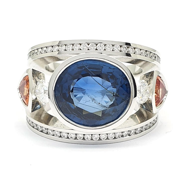 This ring is a unique piece that was handcrafted in Eigenmann's own studio in The Hague.  It is an 18Krt white gold retro ring with 2 triljant sharpened orange corundums and oval sharpened Sri Lanka Sapphire of 9.45c.  The sapphire is a natural