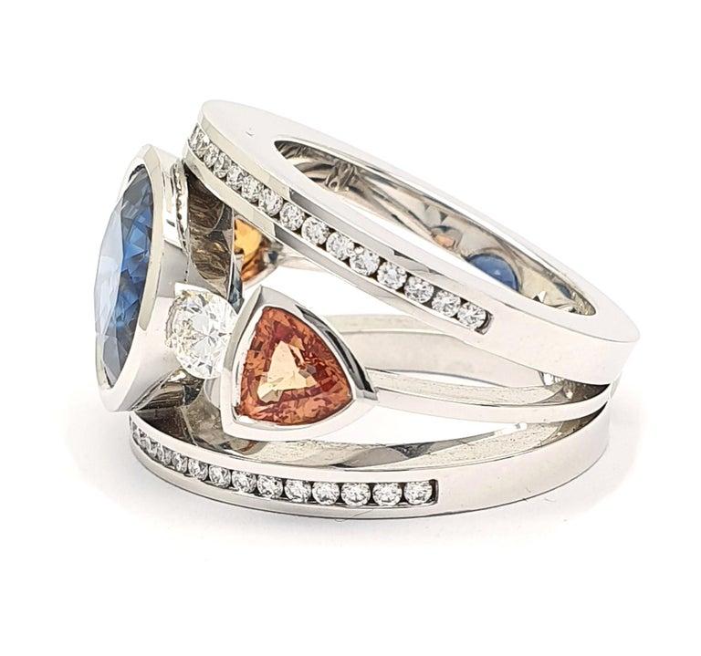 Modern Certified 9.45 Carat Intense Blue Sapphire 2 Orange Corunds and 56 Diamonds Ring For Sale