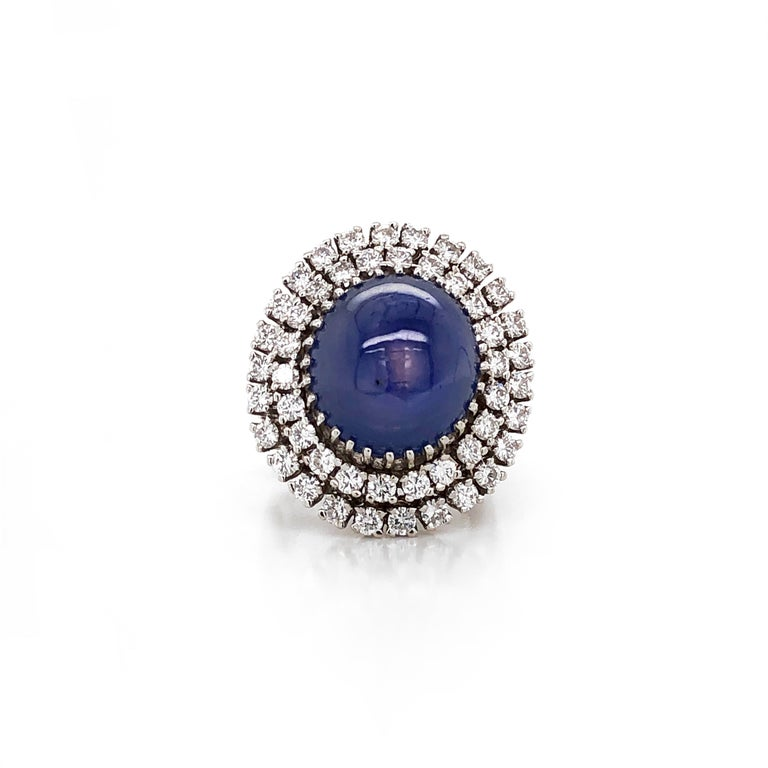 This large and bold cocktail fashion ring holds a cabochon Ceylon blue sapphire 30 ct center stone that is smooth, polished, and slightly reflective. Cabochon sapphire stone is certified and framed by round white round diamonds 0.97 ct.  White